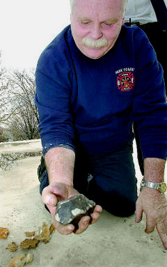 Firefighter Dennis Kennedy holding the meteorite Stephen Carrera